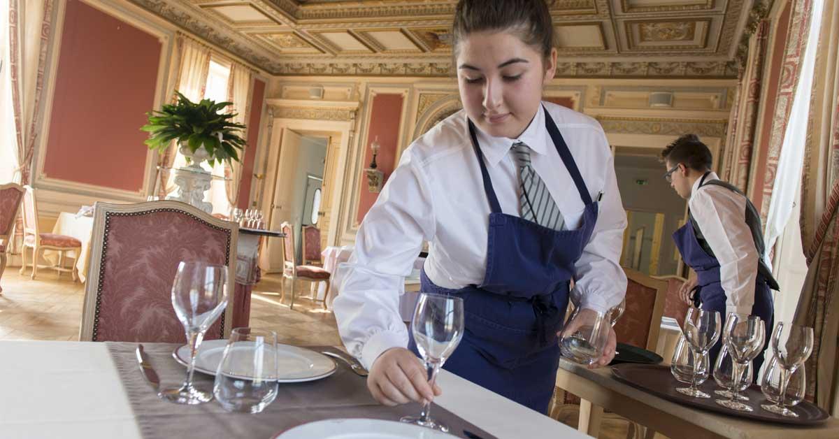 Une jeune femme dresse une table
